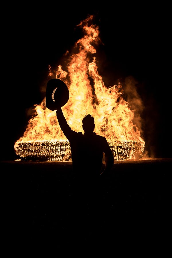 A Plowboy holding up his hat to the bonfire he helped build for homecoming week, 2016