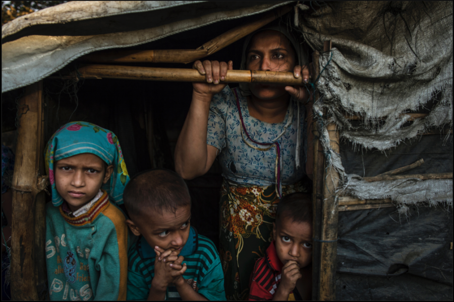 A+Rohingya+family%2C+Burmese+Muslims%2C+live+in+the+Thay+Chaung+camp+for+the+Internally+Displaced+outside+of+Sittwe%2C+which+houses+nearly+3000+people%2C+November+23%2C+2015.+The+mother%2C+pictured+here%2C+claimed+all+her+children+were+malnourished%2C+but+because+of+the+lack+of+medical+professionals+in+the+area%2C+it+was+impossible+to+confirm.+An+estimated+one+million+stateless+Rohingya+have+been+stripped+of+their+citizenship+in+Myanmar%2C+and+forced+to+live+in+modern-day+concentration+camps%2C+surrounded+by+government+military+checkpoints.+They+are+not+able+to+leave%2C+to+work+outside+the+camps%2C+do+not+have+access+to+basic+medical+care%2C+or+food.+Most+aid+groups+are+banned+from+entering+or+working+in+the+camps%2C+leaving+the+Rohingya+to+their+own+devices+for+sustenance+and+healthcare.+Journalists+are+also+routinely+denied+access+to+the+Rohingya%2C+Myanmar%E2%80%99s+way+of+ensuring+the+world+doesn%E2%80%99t+see+the+slow%2C+intentional+demise+of+a+population.