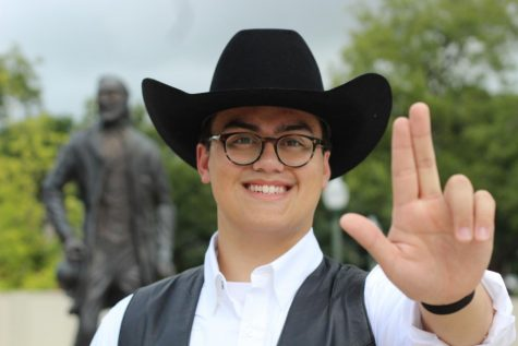Elijah Perry Imbong throws his guns up infront of the John T Statue on Alumni Island.