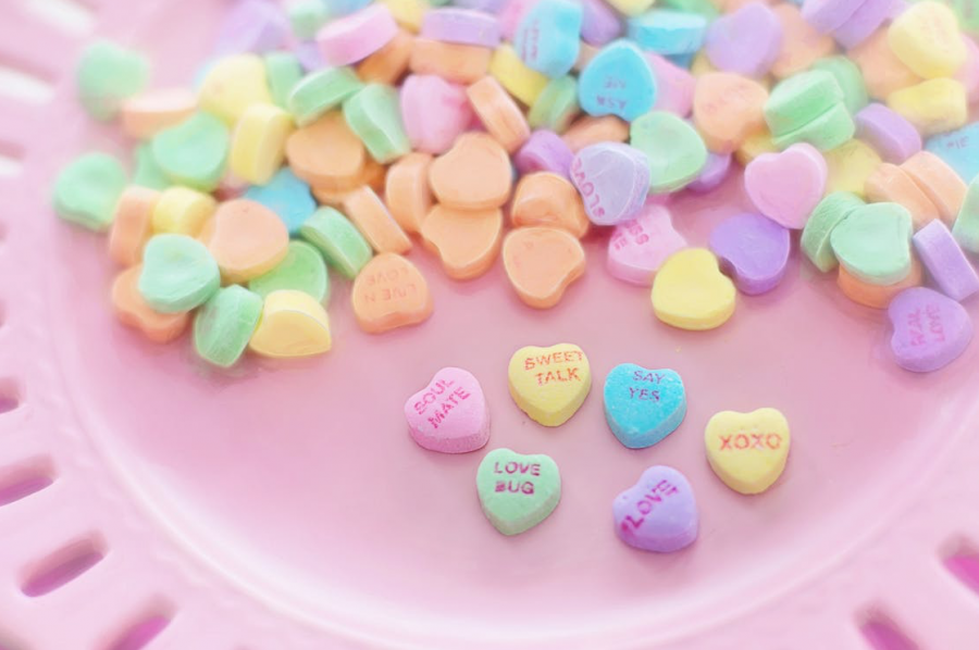 A bowl of candy hearts that give a message on each heart.