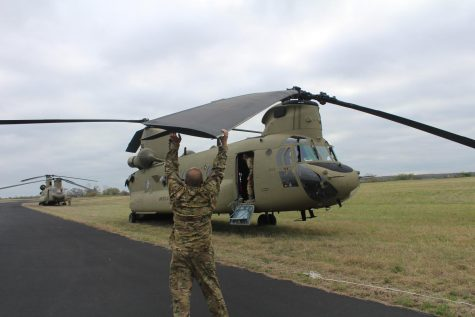 United States National Guard Airman ties down Chinook plane rotors to the ground due to high winds.