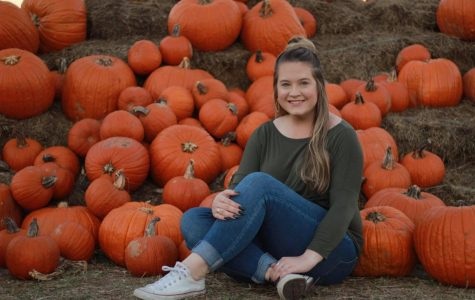 Madison White takes a photo with the pumpkins at Lone Star Family Farm in Stephenville, Texas during Fall of 2018.