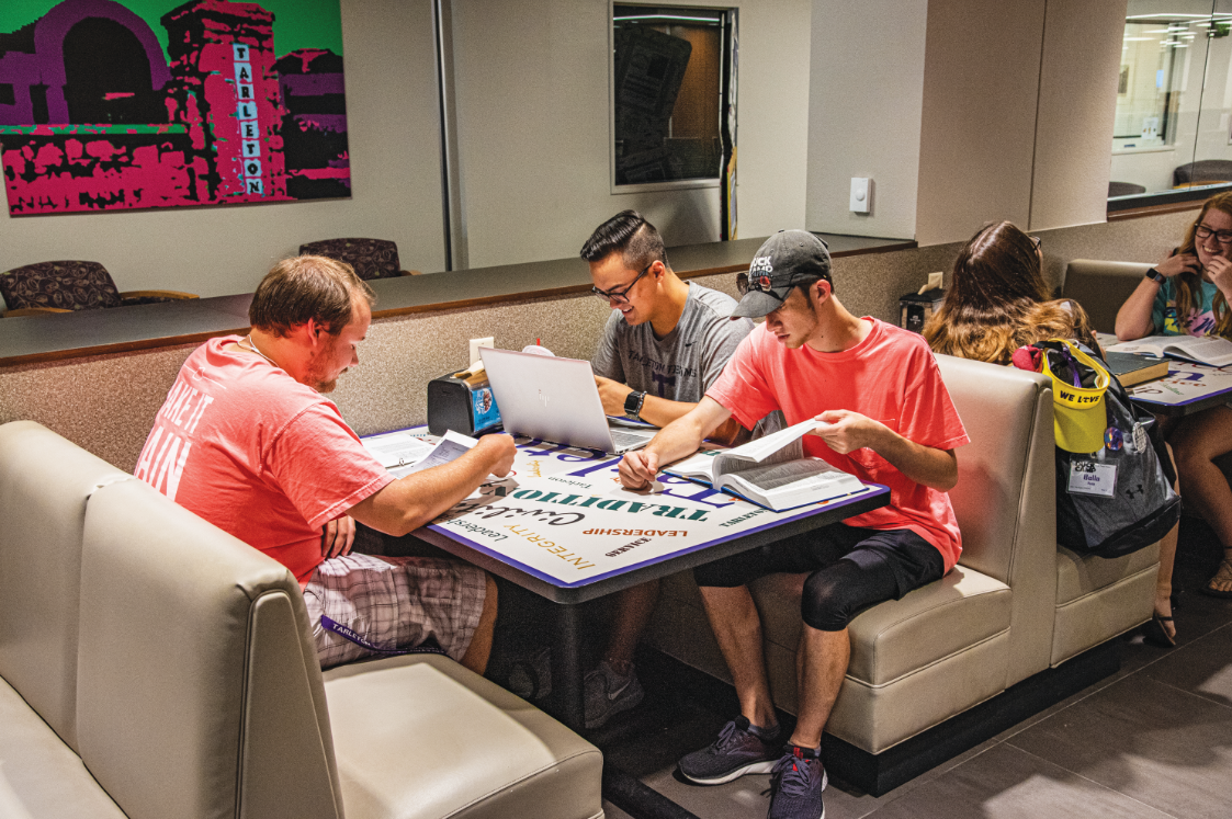 Austin Sikes, Trent Higgins and Elijah Perry Imbong studying on the main floor of the library near Study Grounds.