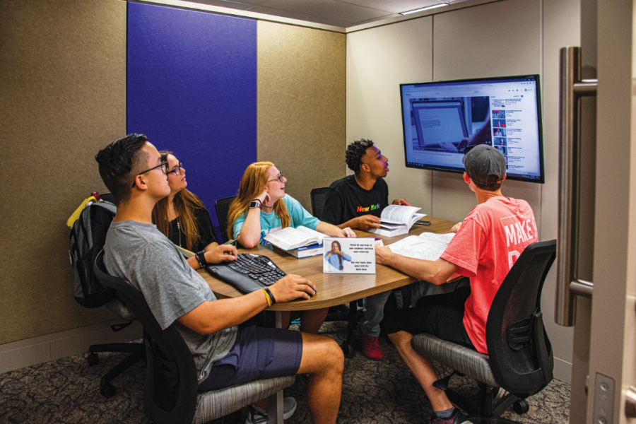 A group of students studying in a collaboration room in the upper level of the library.