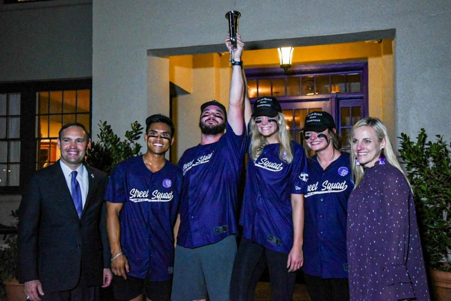 The winning team, The Campus Recreation Street Squad consisted of members Collin Murphy, Hannah McManus, Kaci Bachtel, and Time Khanhaeng holding the Silver Bugle, with Dr. Hurley and his wife Kindall.