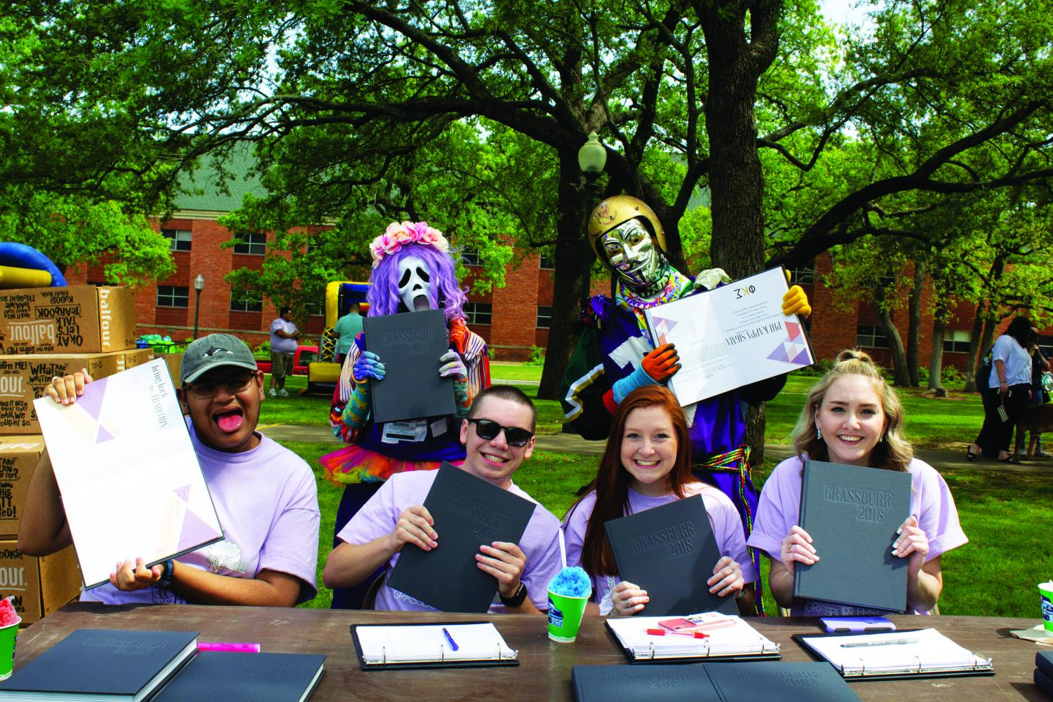 Omar Herera, Joseph Seaman, Hannah Ekwall, and Shelby Smith promote the Grassburr with the Purple Poo. The Grassburr is the official yearbook of Tarleton, started in  1916.