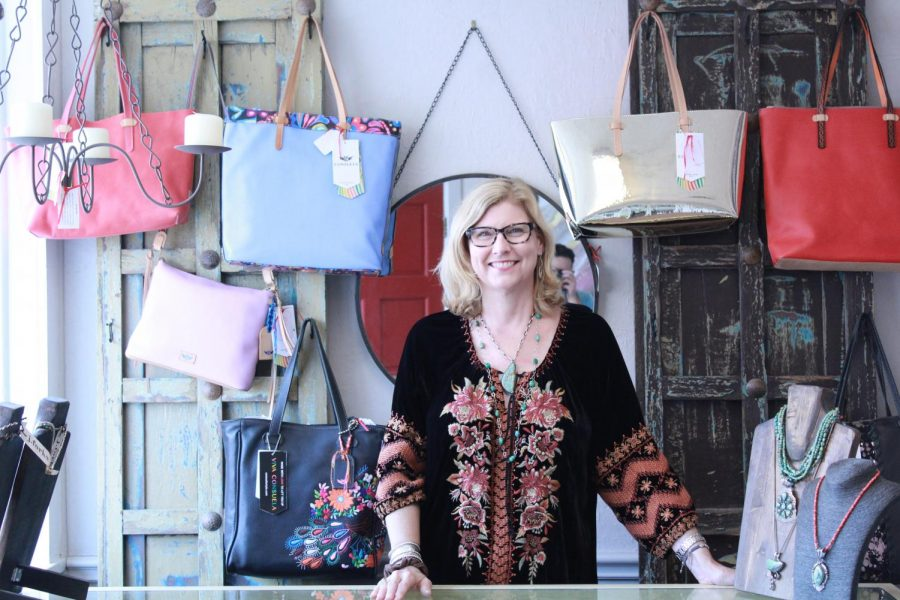 The owner of Willow's Scarlet Ribbon, Laurie Gaiser, poses in front of one of the jewelry and handbag displays in her store.