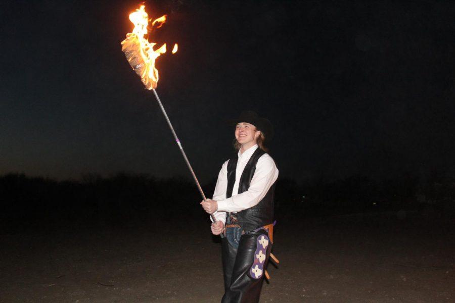Texan Rider, Walker Kirk, lighting his torch at the L.V. Risinger Bonfire on March 19, 2021.