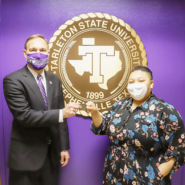 President Hurley presenting winner, Kasey Jones, with a Core Value coin after the presentation of her MLK speech to the President's Cabinet on March 22, 2021.