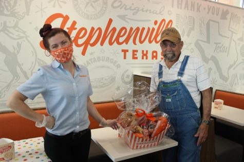 Billy Cowen receiving a gift basket from Whataburger Operating Partner, Minden Sigman, for being the first dine in customer in the new Whataburger store on Washington Street.